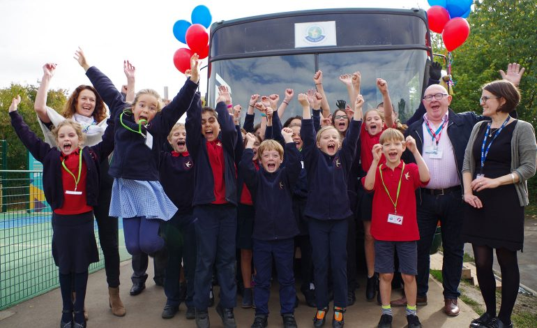 Children celebrate the arrival of the new bus